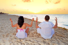 Couple meditating together on the Caribbean Sea. At sunrise Royalty Free Stock Photos