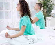 Couple meditating together in their bedroom Royalty Free Stock Image