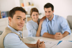 Couple meeting architect in office. Smiling financial adviser with young couple Stock Image