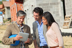Couple meeting with construction manager. Entrepreneur showing house under construction to couple Stock Images