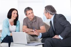 Couple meeting consultant. Happy Couple And Mature Consultant Discussing Together Stock Photos