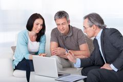 Couple meeting consultant. Happy Couple And Mature Consultant Discussing Together Royalty Free Stock Photography