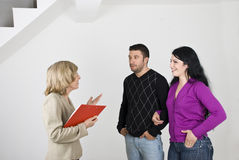 Couple meeting with estate agent. Young couple having a meeting with a senior estate agent and she showing them a new house Royalty Free Stock Image