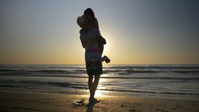 Couple meeting and kissing on the shore and woman jumps in her lover arms in slow motion stock video footage