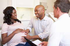 Couple Meeting With Obstetrician In Clinic. Talking To Each Other Smiling Stock Images