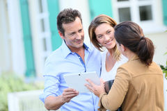 Couple meeting real-estate agent in front of their new home. Couple meeting real-estate agent outside new property Stock Photography