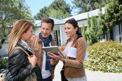 Couple meeting real-estate agent. Real-estate agent with tablet showing house to clients stock photography