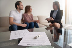 Couple meeting with realtor, focus on rental agreement and keys. Young renters couple sitting on couch discussing renting apartment with real estate agent, focus stock photos