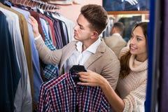 Couple in men's clothes shop. Smiling couple examining various shirts in men's clothes store Stock Images