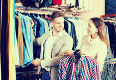 Couple in men's clothes shop. Smiling young men and women examining various shirts in men's clothes store Stock Photography