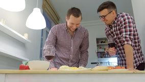 Couple of men gay flirts each other cooking a pizza together and drinking a wine. Couple of men gay flirts each other cooking a pizza together and drinking a stock footage