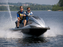 Couple men on jet ski in the river. And one of man shows his tongue Stock Photography