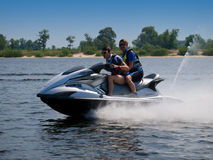 Couple men on jet ski in the river. Couple men on jet ski skim along like an arrow from the bow Stock Photos