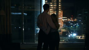 A couple of men and women looking in a large window in a night city. embrace stock footage