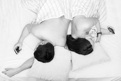 Couple man and woman lying in bed under a blanket with his back stock photos