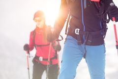 Couple man and woman skier exploring snowy land walking and skiing with alpine ski. Europe Alps. Winter sunny day, snow Royalty Free Stock Images