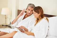 Couple with menu calling room service from hotel Royalty Free Stock Image