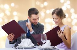 Couple with menus at restaurant stock images
