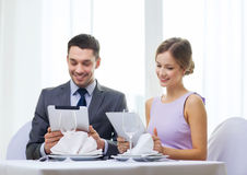 Couple with menus on tablet pc at restaurant Stock Photography