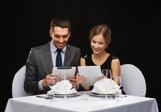 Couple with menus on tablet pc at restaurant. Restaurant, couple, technology and holiday concept - smiling couple with menus on tablet pc computers at restaurant Stock Photos