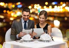Couple with menus on tablet pc at restaurant Royalty Free Stock Image