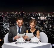Couple with menus on tablet pc at restaurant Stock Image
