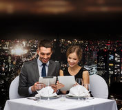 Couple with menus on tablet pc at restaurant. Restaurant, couple, technology and holiday concept - smiling couple with menus on tablet pc computers at restaurant Stock Images