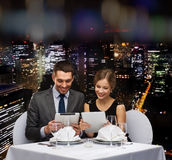 Couple with menus on tablet pc at restaurant. Restaurant, couple, technology and holiday concept - smiling couple with menus on tablet pc computers at restaurant Royalty Free Stock Photography
