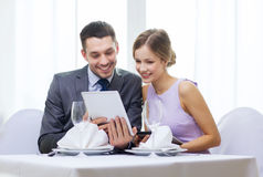 Couple with menus on tablet pc at restaurant Stock Photo