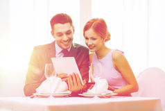 Couple with menus on tablet pc at restaurant. Restaurant, couple, technology and holiday concept - smiling young women looking into boyfriends or husbands menu Royalty Free Stock Image