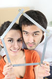 Couple with meter forming a house Royalty Free Stock Photos