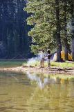 Couple, in mid-distance, fishing near lakeside campfire, woman holding aloft fish, side view Royalty Free Stock Images