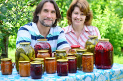 Couple of middle age with homemade preserves and jams. A couple of middle age with homemade preserves and jams Stock Photography