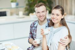 Couple with milk. Happy women and her husband with glasses of milk looking at camera while having breakfast Royalty Free Stock Photos