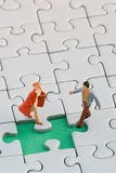 Couple missing piece. A couple standing in front of a missing jigsaw puzzle piece Royalty Free Stock Images