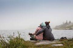 Couple in the mist on the lake footbridge in winter afternoon. Peaceful atmosphere. Foggy air. Couple in the mist on the lake footbridge in winter afternoon Royalty Free Stock Images