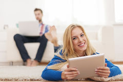 Couple with mobile devices. Beautiful blonde women using digital tablet and relaxing on capet at home Royalty Free Stock Image