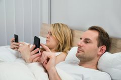 Couple with mobile phones in bed Stock Photos