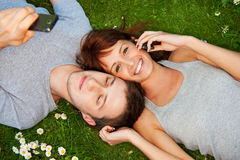 Couple with mobile phones outdoor Royalty Free Stock Image