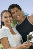 Couple With Mobilephone Enjoying Picnic At Park Royalty Free Stock Photography