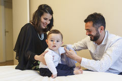 Couple of mom and dad having their baby get dressed. At their bedroom royalty free stock images