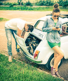Couple in a moment of troubles during a vintage classic car trip Royalty Free Stock Images