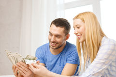Couple with money at home Stock Image