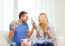 Couple with money and piggybank ot table at home Stock Photography