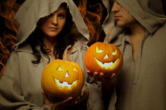 Couple of monks holding halloween pumpkins Royalty Free Stock Photos