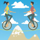 Couple in monocycle over high wire Royalty Free Stock Photos