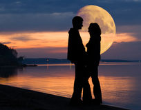 Couple and Moon. Romantic couple and huge Moon behind Royalty Free Stock Photo