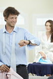 Couple in the morning. Young couple in the morning, man dressing up, cheking time, woman ironing in the background Royalty Free Stock Image