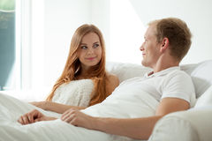Couple during morning in bed. Young couple during morning in bed, horizontal Royalty Free Stock Photos