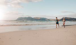 Couple on morning run at the beach Royalty Free Stock Photography